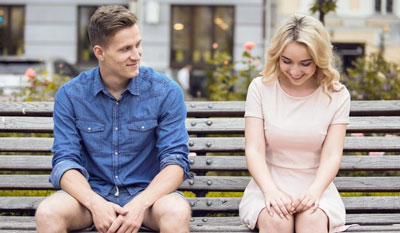 Smitten man looking at cute girl on bench