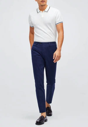 Stylish man with white polo, navy blue pants and black shoes