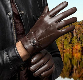 Man putting on leather gloves in autumn