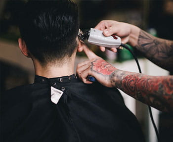 Man getting side of head trimmed by barber