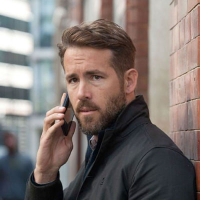 Ryan Reynolds with tapered hair talking on cell phone