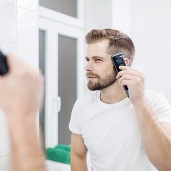Man giving himself a taper fade in mirror