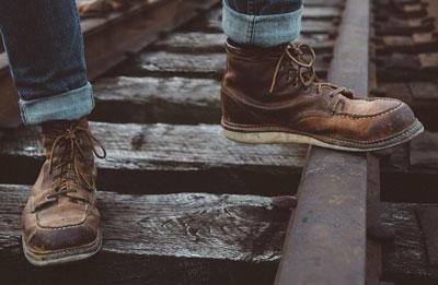 Men's moc toe boots on railroad tracks