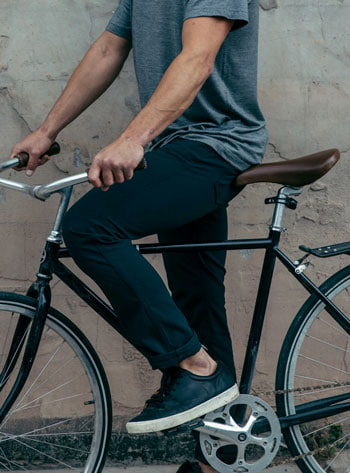 Man wearing Western Rise AT Slim pants on bicycle
