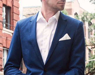 Man wearing blue suit and white pocket square in diamond shape
