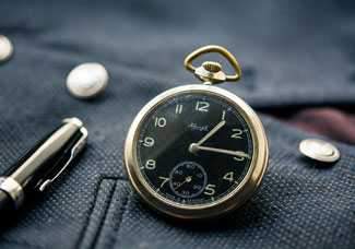 pocket watch and pen laid out on a waistcoat