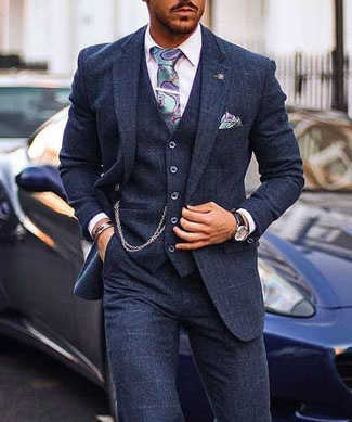 Man wearing a three piece suit and pocket watch in city street