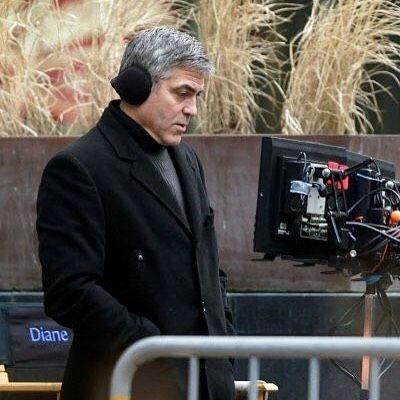 George Clooney wearing ear warmers on movie set