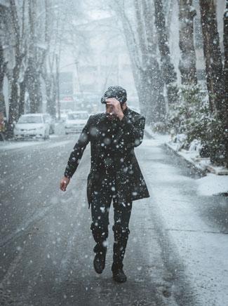 Man walking on snowy street pulls hat down over his eyes