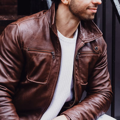 Man wearing brown leather jacket and white sweater