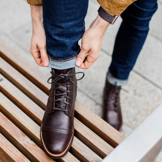 Man rolling up his jeans while wearing Thursday Boot Company's Captain boots