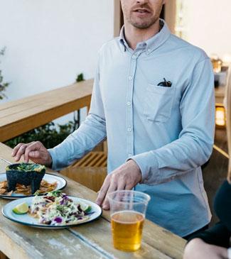 Man wearing Western Rise shirt at outdoor restaurant