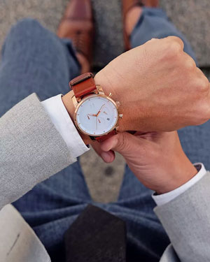 Man looking at a MVMT watch with white face and brown strap