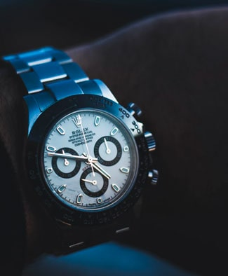 A silver Rolex watch with blue lighting on a man's wrist