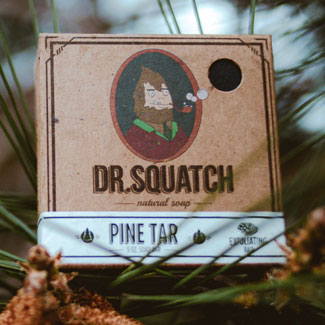 A package of Dr Squatch soap in a pine tree