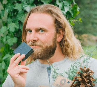 Man smelling Dr Squatch pine tar soap and holding a pine cone