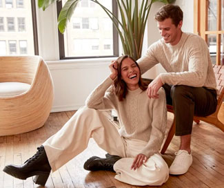 Smiling couple wearing Naadam cashmere sweaters