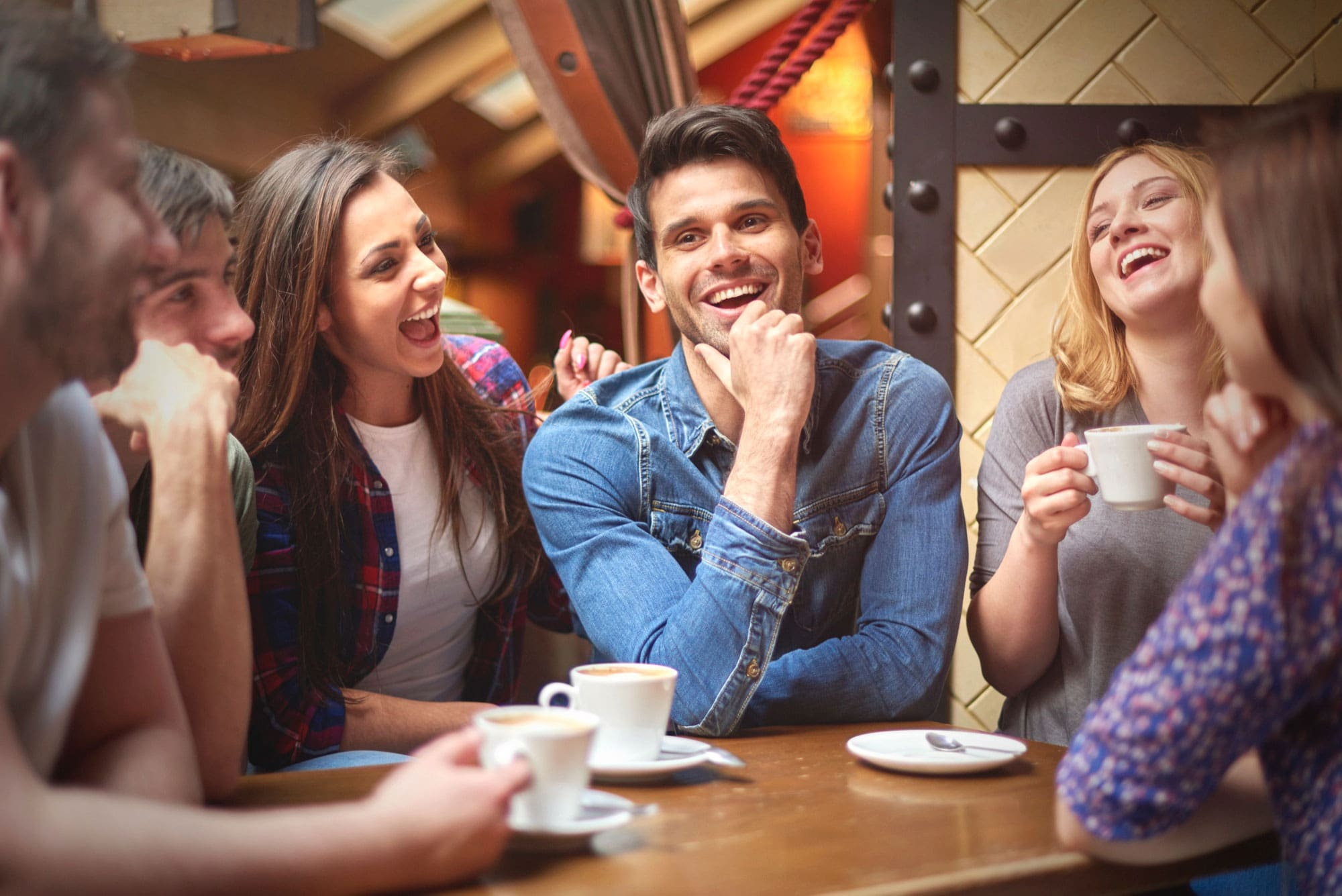 A group of friends laughs while talking at a bar